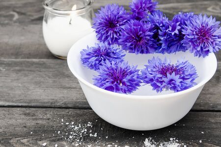 blue cornflowers lie in the water in a white bowl near a burning candle on the background of old boards. close-up