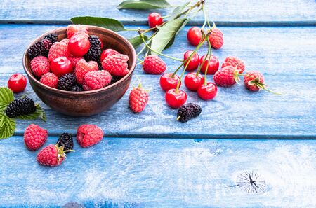 Fruits and berries in a bowl on a blue wooden background. Ripe raspberry, cherry, mulberry. Copy space. Background blend of fruit. Stockfoto