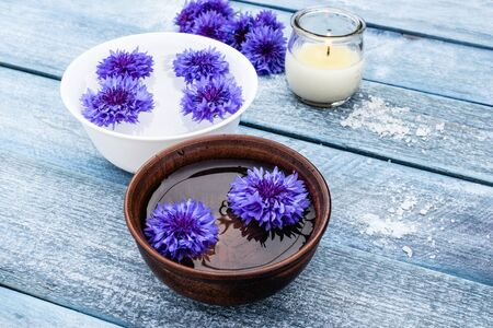 blue cornflowers lie in the water in a bowl near a burning candle on the background of the old blue boards. close-up