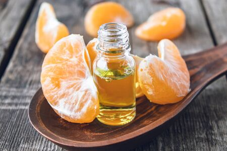 Ripe peeled slices of tangerine without peel and a bottle of essential oil with tangerine on the table. Citrus fruits, tangerines or oranges. Alternative medicine