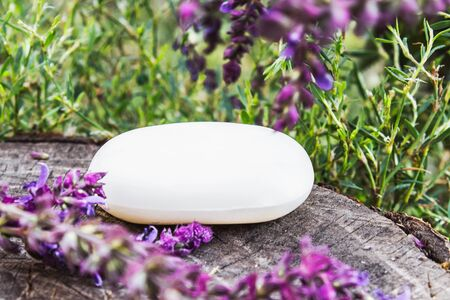 Handmade lavender soap on a wooden background with lavender wildflowers. Soap for the face. Body care. Foto de archivo - 135303118
