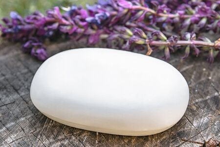 Natural lavender soap with lavender field flowers on a wooden background. Soap for the face. Body care.