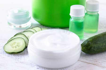 Face cream in a white jar with cucumber extract next to slices of fresh cucumbers on a white wooden background. Spa treatments.