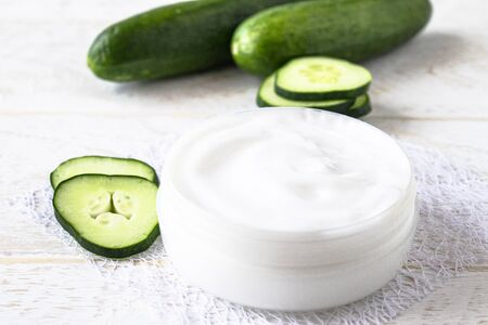 Face cream in a white jar with slices of fresh cucumbers on a white wooden background. Spa treatments.