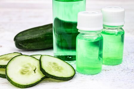 Liquid cosmetics skin care in a bottle and green cucumber with a slice of cucumber on a white wooden table. Natural extract from cucumber. Spa