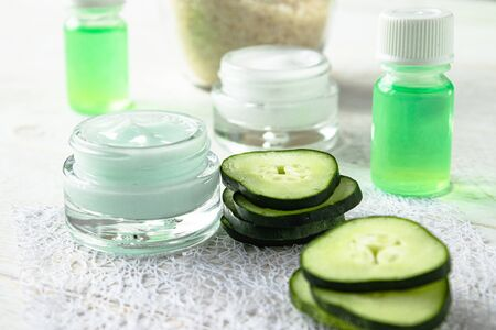 Face cream in a glass jar with cucumber extract next to slices of fresh cucumbers on a white wooden background. Spa treatments. Reklamní fotografie
