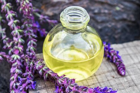 Lavender essential oil in a glass bottle on a wooden table near the branches of blooming lavender. Tincture or essential oil with lavender. Spa herbal medicine.