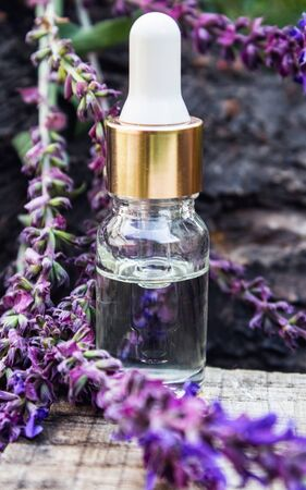 Lavender essential oil in a glass bottle and lavender colors on a rustic wooden background. Tincture or essential oil with lavender. Spa herbal medicine.