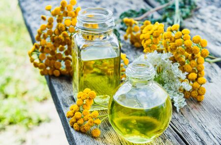 Tansy essential oil in a glass bottle on a wooden background near yellow tansy flowers. Tincture extract with medicinal tansy. Herbal medicine concept. spa 版權商用圖片