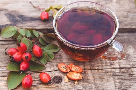 Healing tea with rose hips on a wooden table near red berries. Phytotherapy. Stockfoto