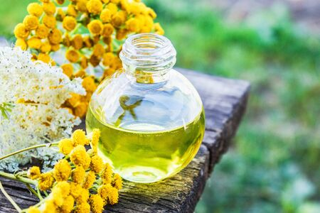 Bottle of tansy and yarrow essential oil or tincture extract on wooden background with yellow tansy and yarrow flowers. Herbal medicine concept. spa 版權商用圖片
