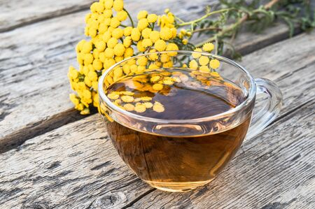 Tansy infusion in a glass cup on a wooden table. Tansy Herbal tea. Healing herbs. Phytotherapy.
