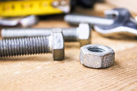 An adjustable spanner lies near the bolts and nuts of the washer against the background of wooden boards. The concept of tools and repair work. 免版税图像