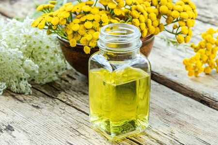 Glass bottle of essential oil or tincture of extract near yellow fresh flowers of tansy and yarrow on wooden background. Herbal medicine concept. spa 版權商用圖片