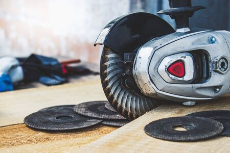 Electric cutting and grinding machine. Angle grinder with abrasive disc on wooden boards. The concept of tools and repair work.