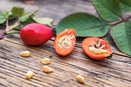 Fresh red rose hips and ripened berries in half with seeds on a wooden table. Close-up. Standard-Bild
