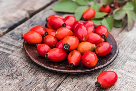 Fresh red rose hips and green leaves on a bowl on a wooden table. Close-up. Banco de Imagens