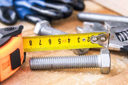 Steel bolt nuts and washers lie on wooden boards near an adjustable spanner and a tape measure. The concept of tools and repair work.