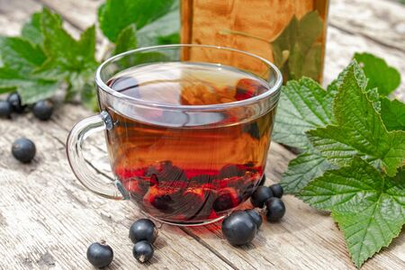 Tea in a glass cup of black currant on a wooden table near a glass teapot on a background of green grass. Close-up.