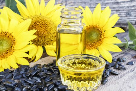 Sunflower oil with seeds on a wooden background near fresh sunflower flowers. Organic and eco food. Healthy foods and fats.
