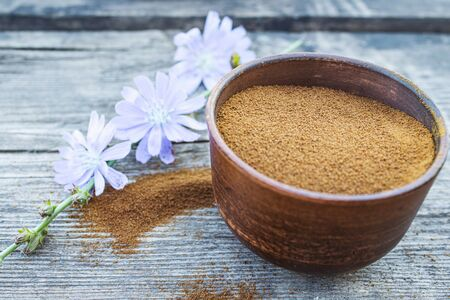 Blue chicory flower and a bowl of instant chicory powder on an old wooden table. Chicory powder. The concept of healthy eating a drink. Coffee substitute.