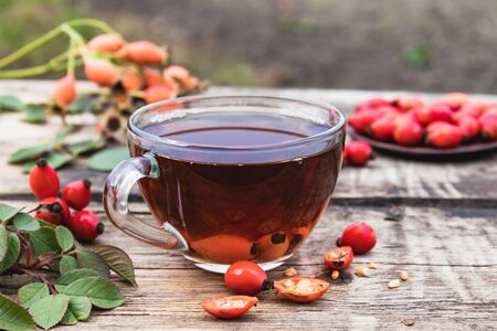 Tea or tincture with rose hips in a glass cup near red berries on a wooden table. Phytotherapy.