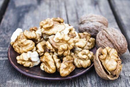 Walnut kernels lie in a bowl on a rustic old wooden table. Fresh walnuts. Harvest walnuts.