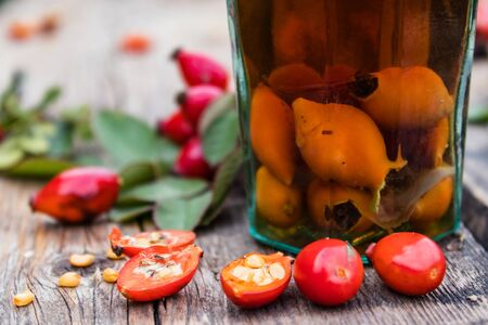 Glass bottle with tincture or a drink with rose hips on a wooden table near the red berries of rose hips. Phytotherapy. Banco de Imagens