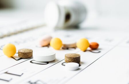 A bunch of different pills on a calendar background. Pills, supplements and medicines for the disease. Healthcare Foto de archivo