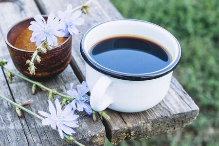 Cup with chicory drink and blue chicory flowers on a wooden table. Chicory powder. Healthy eating concept. Coffee substitute. 스톡 콘텐츠