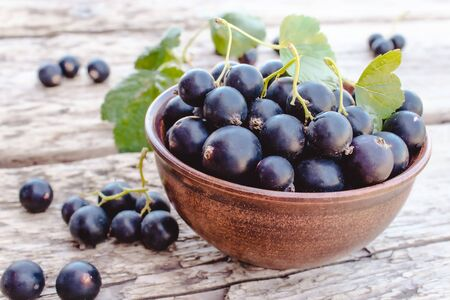 Fresh ripe currant berries in a bowl on a wooden background near green leaves. Juicy natural fruits currant. Black currant