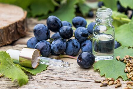 Grape seed oil in a glass jar and fresh grapes on old wooden boards. The concept of SPA, Bio, Eco products.
