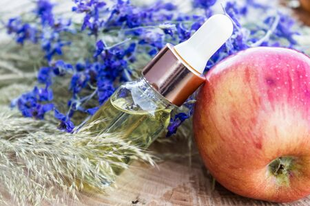 Glass bottle of apple essential oil near fresh apples on a wooden table. Essential oil is used to fill lamps, perfumes and in cosmetics. Close-up.