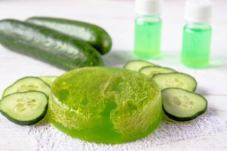 Green cucumber soap on a white background with cucumber slices and cucumber tincture extract in a bottle. Spa treatments with cucumber soap. Body care.