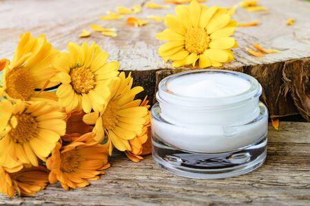 Ein Glas weiße kosmetische Creme zur Körperpflege. Frische orange Calendula-Blumen auf hölzernem Hintergrund. Medizinische Dermatologie.