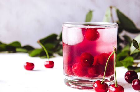 A glass of cherry drink with ice in a glass on a white wooden background. Fresh summer cocktail with cherries and ice cubes. Close-up. Imagens