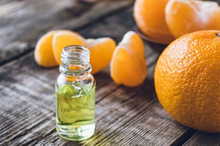 A glass bottle of essential oil with mandarin and slices of ripe mandarin are on the table. Citrus fruits, tangerines or oranges. Alternative medicine Reklamní fotografie