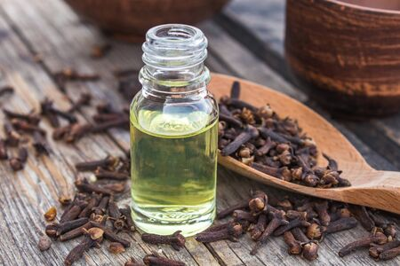 A bottle of clove essential oil stands near a spoon with clove spices on old wooden boards. Phytotherapy.