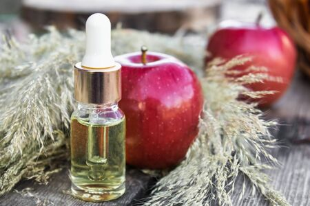 Apple essential oil on a wooden table near ripe red apples. Essential oil is used to fill lamps, perfumes and in cosmetics. Close-up. Reklamní fotografie