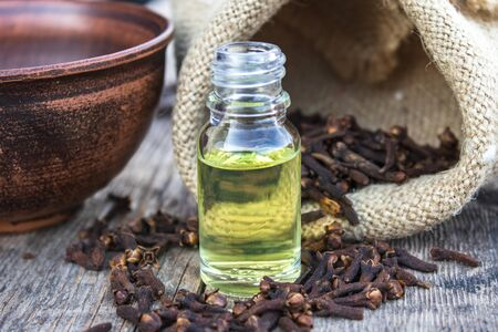 Spice clove essential oil in a glass bottle on old wooden boards near dry clove spices. Phytotherapy.