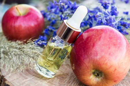 Bottle of apple essential oil and fresh apples on a wooden table. Essential oil is used to fill lamps, perfumes and in cosmetics. Close-up.