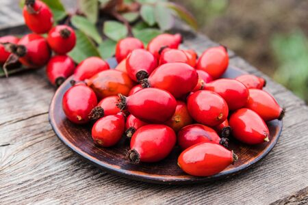 Fresh red rose hips and green leaves on a bowl on a wooden table. Close-up. Standard-Bild