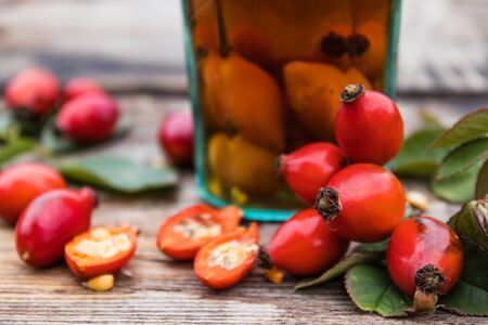 Tincture in a glass bottle with red rosehip berries on a wooden table. Phytotherapy.