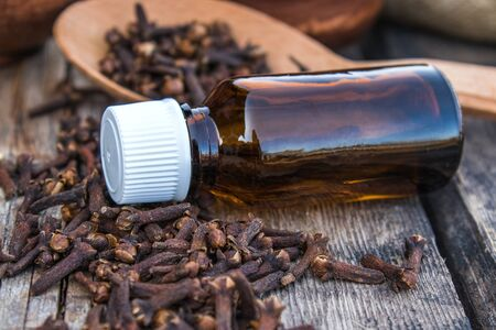 Clove essential oil in a dark glass bottle and dry clove spice on old wooden boards. Phytotherapy.