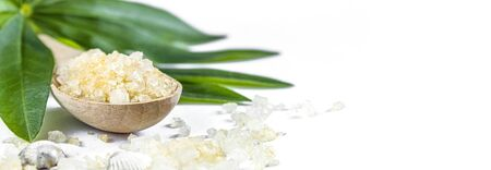 Spa banner cosmetic treatment concept. Sea resort salt, yellow solv spoon and green leaves on a white background. Copyspase flatlay