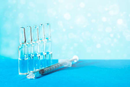Medical ampoules for injection, vial and syringe on a blue background. Glass ampoules and vials of medicine on the table. Medicines and disease treatment, pharmacology and scientific concepts