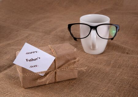 gift box on the table. Near a cup with glasses on. Fathers day concept.