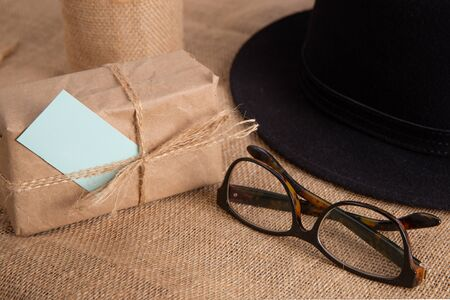 Gift box on the table.Nearby glasses and hat.Fathers Day congratulation concept