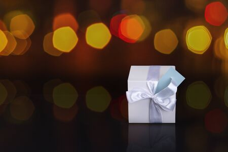 Gift box with bow and card. Blurred background. Space for text.