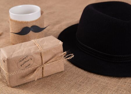 gift box on the table. Next to a cup with a glued mustache.